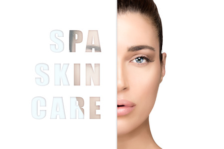 Spa Skin Care concept with a beautiful young woman wearing natural makeup in a half face close up cropped beauty portrait with a white sign with the text