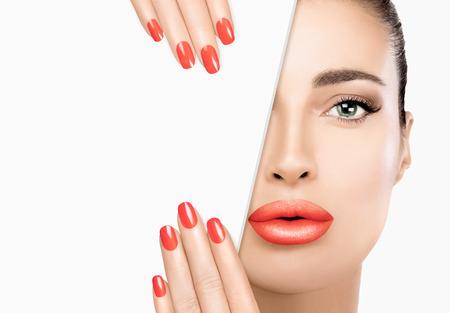 Preciosa modelo de belleza con labios carnosos con maquillaje coral de moda, ojos ahumados suaves y base sobre una piel sin manchas. Foto de archivo