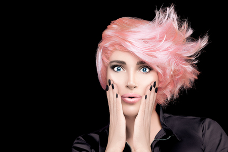 Fashion model girl with stylish rose gold hair, hands on cheeks and wow expression looking at camera.