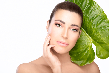 Spa beauty portrait of a serene young woman with smooth flawless complexion and subtle makeup in a skincare or natural treatment concept holding a hand to her cheek with a green tropical leaf on white