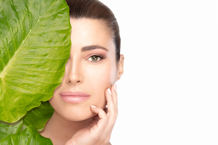 Skin care concept with a young beautiful woman with perfect soft skin touching her face while looking at camera from behind a big green leaf. Studio shot portrait isolated on white with copy space