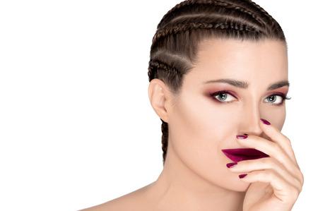 Belle jeune femme de mode aux cheveux tressés portant un rouge à lèvres, un vernis à ongles et un fard à paupières assortis. Concept de beauté et de maquillage. Visage agrandi isolé sur blanc avec espace de copie. Banque d'images