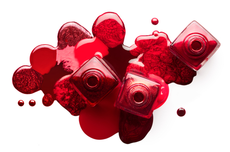 Fine art cosmetics image of open red nail polish bottles with different shades, viewed from above. Pools of polish spilled on white background Фото со стока