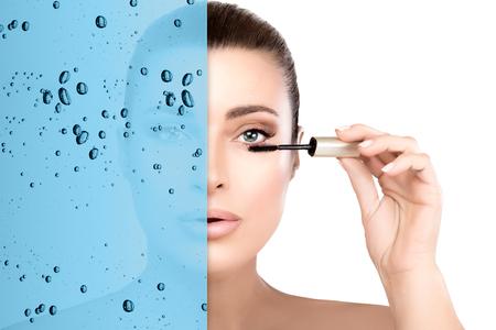 Schönheitsporträt einer jungen Frau mit makelloser natürlicher Haut, die Mascara auf ihre Wimpern aufträgt, die halb mit frischem blauem Wasser mit Blasen in einem Augenpflege- und wasserdichten Mascara-Konzept überlagert ist. Standard-Bild