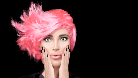 Fashion model girl with stylish pink hair, hands on cheeks and wow expression looking at camera. Beauty salon hair coloring concept. Beauty Hairstyle portrait isolated on black with copy space.