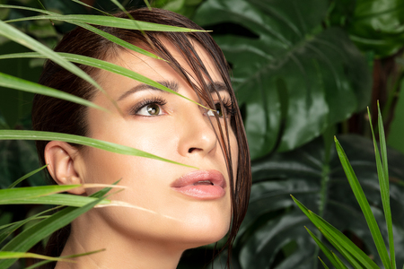 Beauty and health concept. Closeup portrait of a beautiful young woman face with flawless smooth skin wearing subtle makeup surrounded by green tropical plants