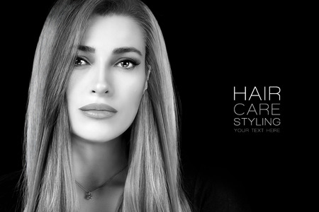 Beautiful young woman with healthy long hair and a smooth flawless skin looking at camera . Hair care, salon and styling concept. Close up beauty portrait isolated on black with copy space