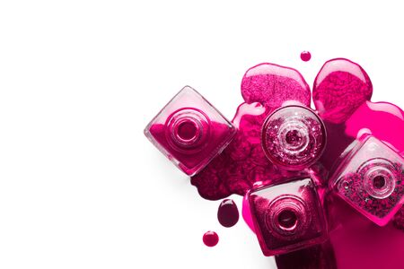 Nail art concept. Fine art cosmetics and beauty image of a group of four nail polish bottles on spilled metallic pink paint with copy space for text.