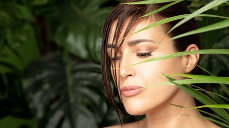 Closeup portrait of a beautiful woman with a flawless smooth skin wearing subtle makeup surrounded by green tropical plants in a natural skin care concept.