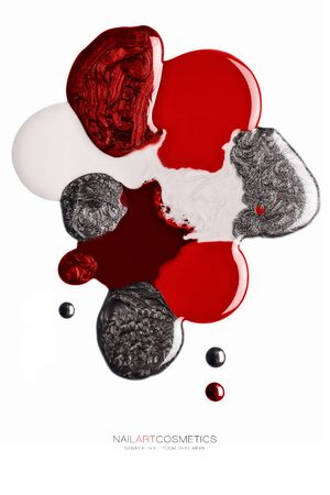 Artistic blend of various shades of red and silver ink. nail polish spilled in fused blobs giving an abstract shape isolated on white in a fashion and beauty concept.