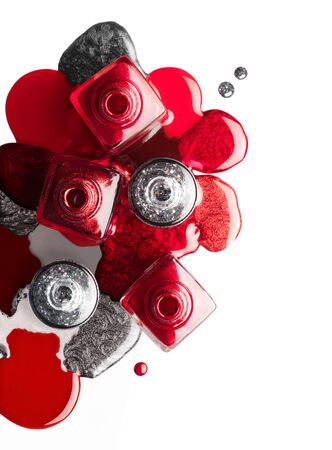Fine art cosmetics and beauty image. Nail art concept with a set of trendy red and silver nail polish spilled around four opened bottles, top view isolated on white with copy space