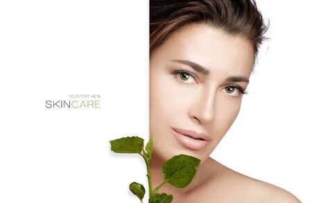 Beautiful natural young woman with flawless skin and nude makeup holding fresh green leaves to her face in a half portrait with white lateral copy space conceptual of organic and bio skincare products