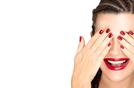 Beauty portrait of a laughing woman with braided hair covering her eyes with hands showing a subtle makeup, red nail varnish and matching red lipstick
