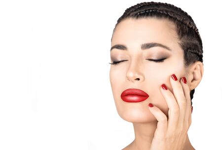Beautiful young woman with braided hair, red lips and nails and smokey eye make up touching her cheek with closed eyes and a serene expression over white in a beauty and makeup concept
