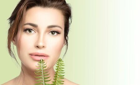 Natural skincare, health and wellness concept. Beautiful young woman with flawless skin and subtle makeup looking at camera holding fresh green leaves near to mouth.