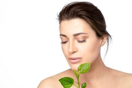 Beauty portrait of a young woman with flawless skin wearing subtle makeup with downcast eyes holding fresh green leaves near to chin in a natural skincare