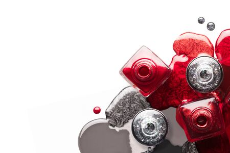 Fine art cosmetics and beauty image. Nail art concept with a set of red and silver nail polish spilled around four opened bottles