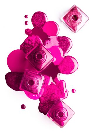 Nail art concept. Fine art cosmetics and beauty image of a group of four nail polish bottles on spilled colorful pink paint. Zdjęcie Seryjne