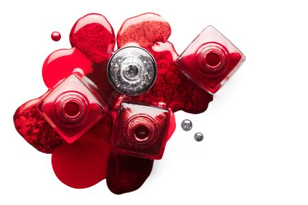 Fine art cosmetics image of open red and silver nail polish bottles with different shades of metallic color, viewed from above.