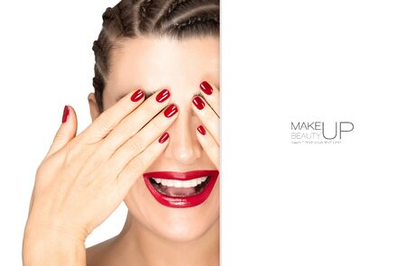 Beauty and makeup concept. Laughing model girl with braided hair covering her eyes with hands, subtle makeup, red nail varnish and matching red lipstick.