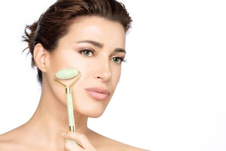Beautiful young brunette woman using a jade face roller on her flawless skin. Beauty face closeup. Conceptual of facial treatments with semi precious stones. isolated on white with copy space