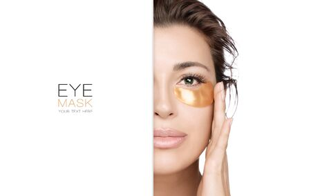 Eye skin care. Brunette woman with golden eye mask. Beautiful girl using collagen patches to prevent skin aging. Closeup beauty portrait isolated on white with copy space.