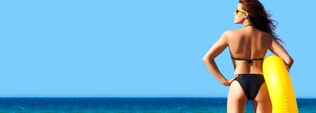 Sexy suntanned woman in black bikini standing holding a big yellow inflatable ring while looking out over a calm blue ocean in summer sunshine conceptual of travel and summer vacations, panorama view.