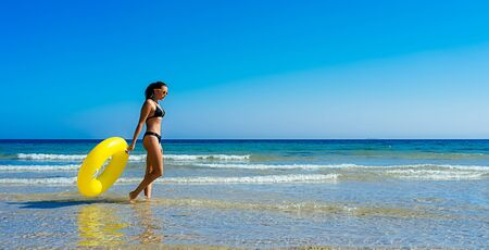 Young woman on vacation in bikini with a giant yellow float walking along the seashore. Holiday lifestyle scene
