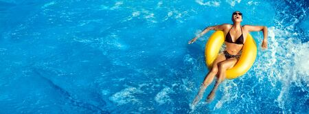 Summer vacation, Laughing young woman enjoying an aqua park with a yellow float on sparkling blue water in a pool with turbulence and copy space in an overhead panorama