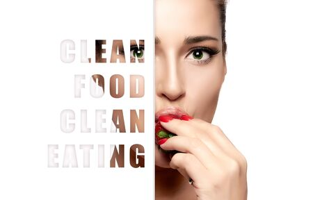 Clean food and clean eating concept with a cropped half portrait of a beautiful sensual young woman with red nails and subtle makeup eating a fresh ripe strawberry isolated on white