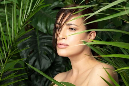 Beautiful young woman with a flawless skin and natural make up standing amongst fresh green tropical leaf fronds looking aside. Natural bio cosmetics and skin care concept Zdjęcie Seryjne