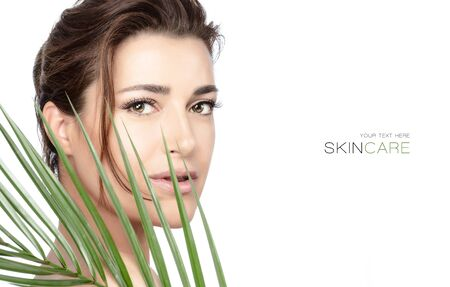 Beautiful model woman face with healthy clean fresh skin and long lashes holding a green tropical leaf.