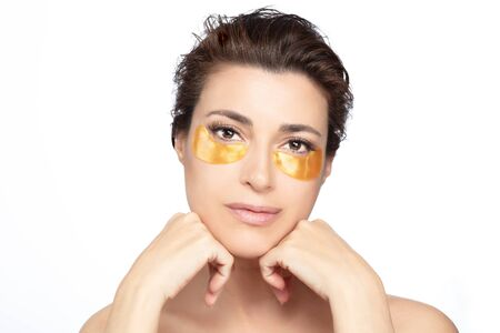 Woman with under eyes collagen pads, beauty face with healthy fresh skin, anti-aging hydration with gold hydrogel patches
