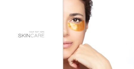 Woman with under eye collagen pad, beauty face with healthy fresh skin. Skin care concept, anti-aging moisturizer eye mask, gold hydrogel patches. Half face portrait with copy space 写真素材