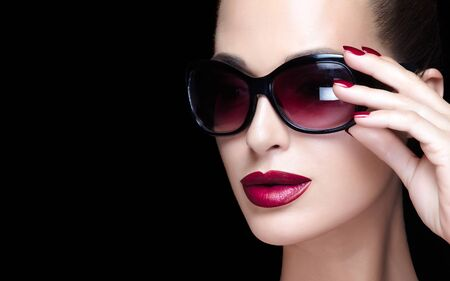 Stylish woman with perfect makeup and trendy glasses. Beautiful model girl with bright makeup, red juicy lips matching with perfect manicure and elegant oversize sunglasses. High fashion portrait. 写真素材 - 133590078