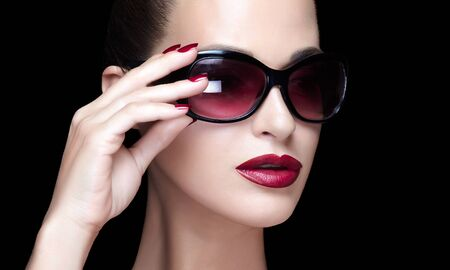 Face of a stylish beautiful woman with deep crimson lips and natural foundation makeup wearing fashion shaded sunglasses holding her hand with manicured nails to the frame on black with copy space 写真素材 - 133590081