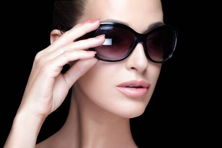 Fashion model girl with nude makeup posing with big sunglasses. Pretty woman face with nude makeup, juicy lips and perfect manicure wearing elegant glasses. Close up portrait isolated on black 写真素材 - 133590099