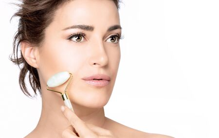 Beautiful brunette woman with healthy clean fresh skin massaging her cheek with a face roller to tone and relax the muscles and improve circulation isolated on white with copy space