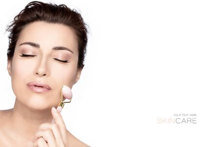 Beautiful woman with healthy fresh clean skin using a pink quartz face roller. Beauty skin care or spa skin care treatment concept isolated on white with copy space Stock fotó
