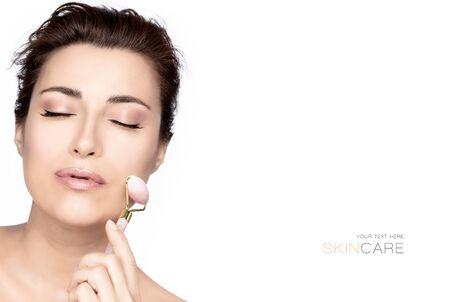 Schöne Frau mit gesunder frischer, sauberer Haut mit einer rosa Quarz-Gesichtsrolle. Beauty-Hautpflege- oder Spa-Hautpflege-Behandlungskonzept isoliert auf weiß mit Kopierraum Standard-Bild