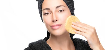 Healthy skin woman cleans her facial skin with a cosmetic sponge pad. Youth and skin care concept. Beauty routine banner. Beautiful young woman with black bathrobe and towel in head with a peeling cosmetic product