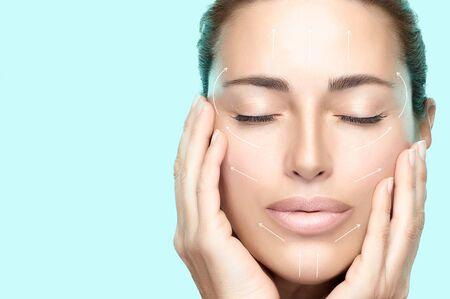 Concept de traitement anti-vieillissement et de chirurgie plastique. Belle jeune femme à la peau fraîche et propre les mains sur les joues et les yeux fermés, expression sereine. Flèches blanches sur le visage. Isolé sur blanc. Espace de copie