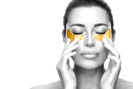 Beauty model face with gold hydrogel patches under eyes. Beauty and skin care concept. Beautiful woman with healthy fresh skin using cosmetic eye mask. Eye skin rejuvenation treatment. Copy space