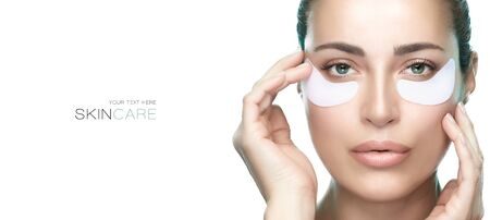 Eyes cosmetic mask. Beautiful woman with healthy fresh skin using patches under eyes. Beauty and eye skin care banner. Eye skin rejuvenation treatment. Isolated on white background with copy space