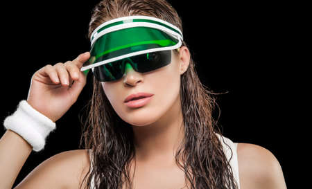 Sporty attractive young woman with long wet hair, sunglasses and sun visor looking at the camera. Healthy sports lifestyle concept Banco de Imagens