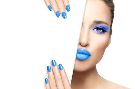 Beauty Makeup and Nail Art Concept. Beautiful fashion model girl with blue makeup, perfect skin and trendy cyan nails, half face with a white card template. High fashion portrait isolated on white