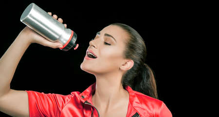 Sporty beautiful sensual young woman with her long hair tied back in a ponytail preparing to drink from a flask with mouth open and eyes closed, panorama over a black background with copyspace