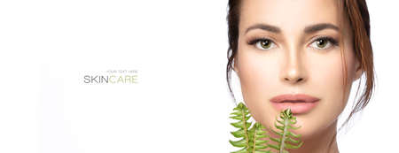 Beauty and skin care concept. Beautiful natural young woman face with makeup on a flawless skin looking at camera holding fresh green leaves to her chin. Skincare, health, wellness and spa banner
