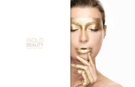 Gold based anti aging skincare concept. Beautiful model woman with gold treatment on a flawless skin posing with closed eyes and a serene expression. Close up beauty portrait isolated on white