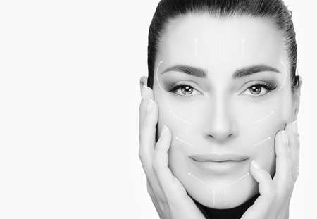 Anti aging treatment and plastic surgery concept. Beautiful young woman with hands on cheeks looking at camera with a serene expression. Flawless skin. Monochrome close-up portrait on white with copy space for text.